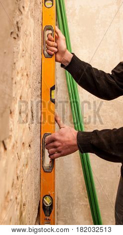 Master Used Spirit Level To Check Whether The Wall Plane
