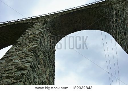Bottom view on the stone railway viaduct with electrical wires.