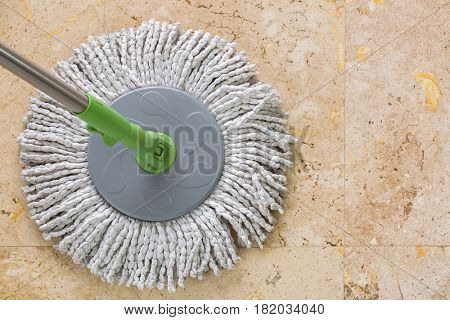 Used round spin mop with microfiber head, green handle on yellow granite tiles floor with copyspace
