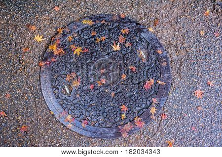 KyotoJapan-November 26 2015 : The old manhole cover with red maple onthe ground at Arashiyama village in Kyoto Japan.