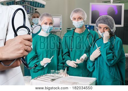 Doctor holding stethoscope over surgeons team prepare to operation.