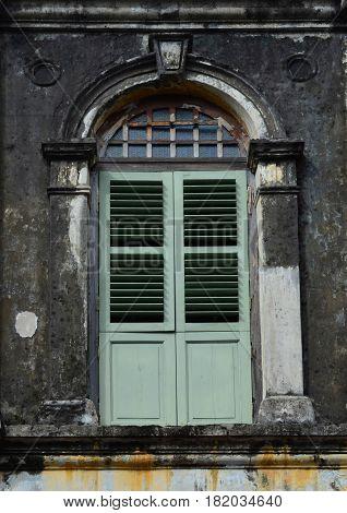 Green wooden window on grunge vintage facade wall