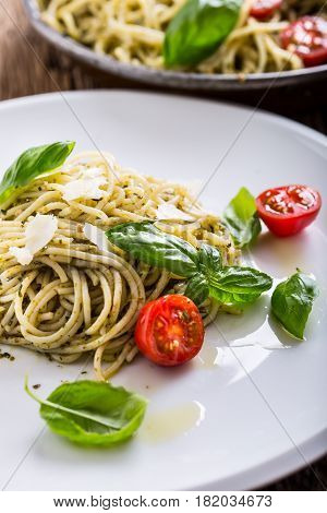 Spaghetti. Italian pasta spaghetti with basil pesto cherry tomatoes and olive oil.