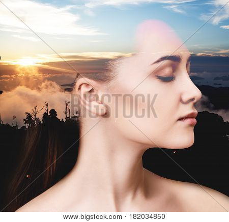 Double exposure portrait of woman and sunset sky