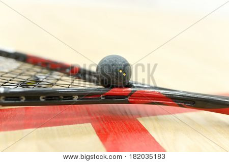 squash racket and ball on the floor near red lines. Closeup of racquetball equipment on the court. Photo with selective focus. Sport, games on the court, healthy lifestyle concept