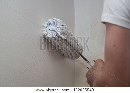 Painter Whitewashed Wall With White Paint Roller In Hand