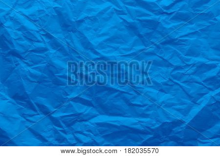 Background of a crumpled blue paper. Wrinkled paper close-up