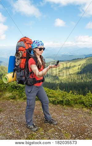 woman tourist in mountains determines the direction with a compass. Hiker girl holding compass. Healthy lifestyle, adventure, active leisure tourism and hiking trip concept