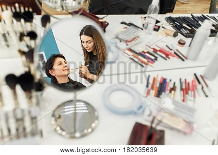 professional makeup artist doing anti-aging makeup for middle aged women. Make-up artist work in beauty salon. Real people. Reflection in the mirror as visagiste applying makeup. Backstage photo