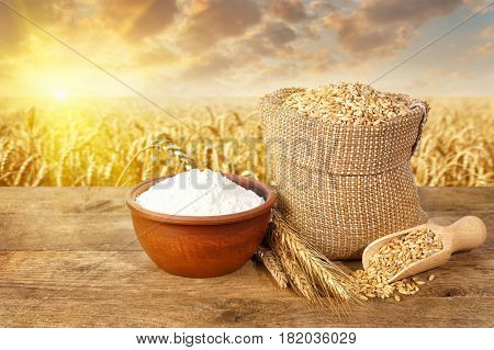 still life ears of wheat and grains in bag and flour in bowl on table with ripe field on the background. Agriculture and harvest of bread concept. Golden wheat field on sunset