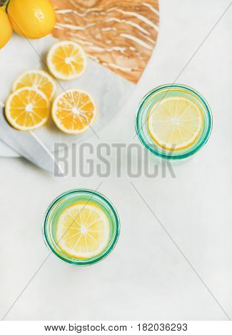 Morning detox lemon water in glasses served with fresh lemon fruits over light grey marble background, top view, copy space. Clean eating, weight loss, healthy, detox, dieting concept