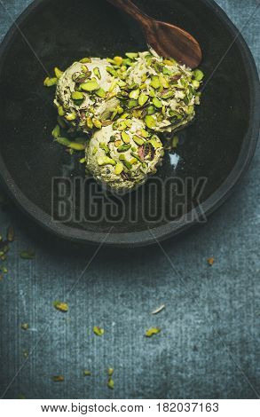 Homemade pistachio ice cream scoops with crashed pistachio nuts in dark bowl over grey concrete background, top view, copy space