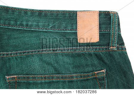 Leather label on green jeans. Green denim fabric