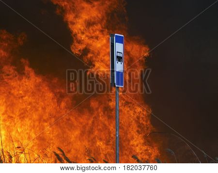The sign of the bus stop and the flame of fire behind it