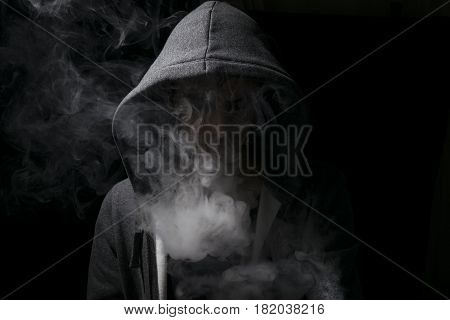 Vaping Man Wearing A Hoody With Lots Of Smoking Clouds.