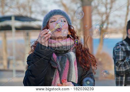 Volgograd Russia - April 01 2011: Portrait of young woman blowing soap bubbles on a flashmob in Volgograd