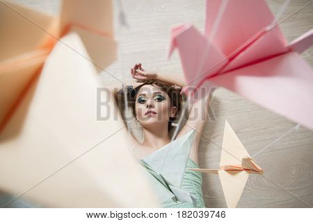 Girl in a pistachio-colored dress dreams on the background paper of birds. Origami cranes dragons. Romantic delicate image of a girl