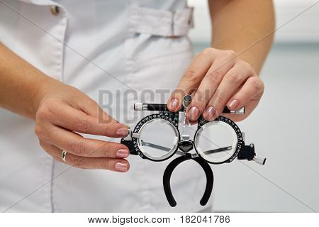 Hands of female doctor hold ophthalmic glasses and lens.