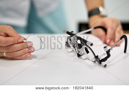 Hands of female doctor, ophthalmic glasses and lens, shallow dof.