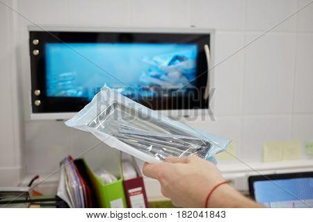Doctor hand holding pack of medical tools against ultraviolet sterilizer.