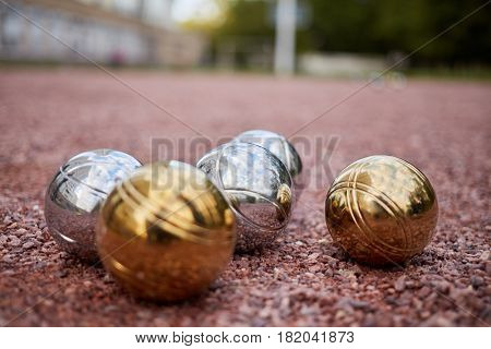Group of petanque balls lying on ground, shallow dof.