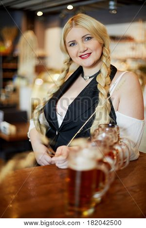 Smiling blonde woman stands holding spikelet in hand and leaning elbow on bar counter with beer mugs in cafe.
