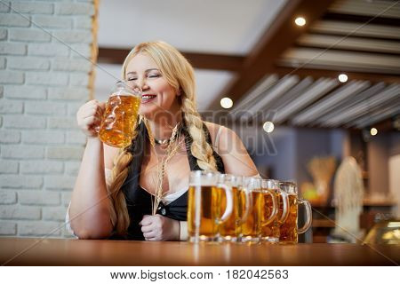 Smiling blonde woman stands holding spikelets in one hand and going to drink beer from mug in another at bar counter in cafe.