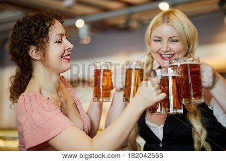 Two smiling women clang glass mugs with beer.