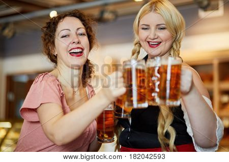 Two laughing women clang glass mugs with beer. poster