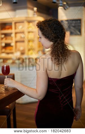 Woman in red slinky evening dress with glass of beverage at bar counter, rear view.