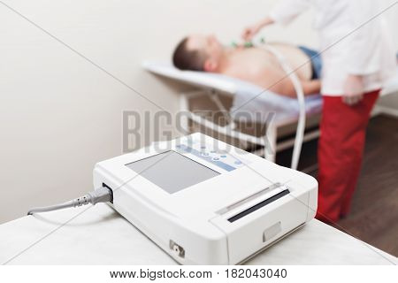apparatus or device the unit of measurement of the electrocardiogram in a doctor's office. Male patient having ECG electrocardiogram in hospital. selective focus.