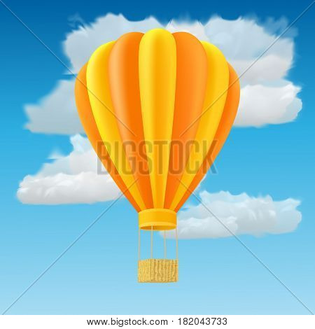 Yellow and orange air ballon with basket fly past clouds