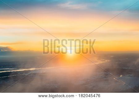 Top View Of Sunset Sunrise Over Earth. Aerial View From High Altitude Flight Of Aircraft On Sunny Sunset Sunrise In Winter. Sunny Dawn Sky.