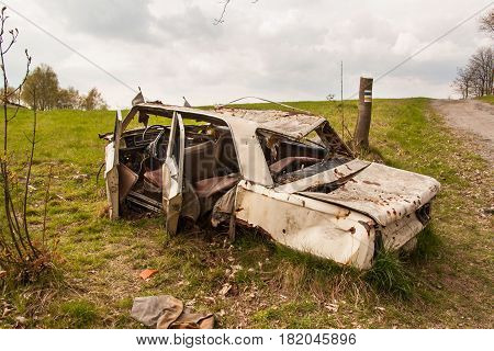 Wreck car on a dirt road. Disassembled vehicles. A cloudy spring day