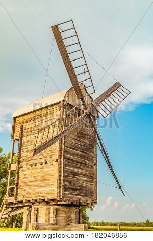 Antique wooden flour windmill. Historic agricultural building.