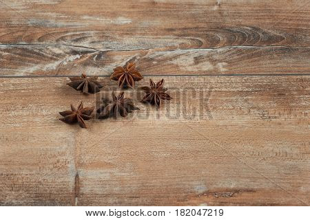 А Star anise on brown wooden background.