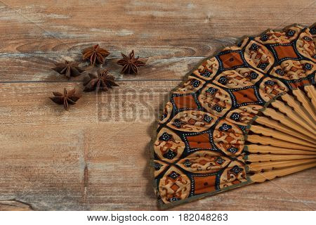 Star anise and fan on brown wooden background.