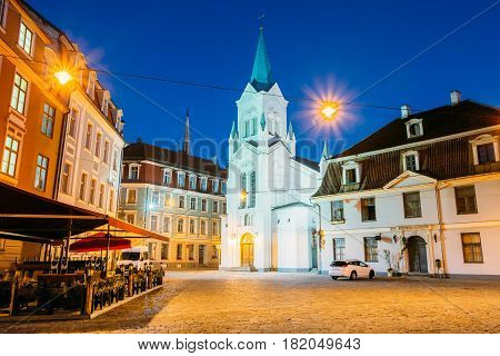 Riga Latvia. Main Facade Of Virgin Of Anguish Or Our Lady Of Sorrows Church, Ancient Catholic Church On Pils Street In Evening Illumination In Summer Among Original Architecture Of Old Town, Blue Sky