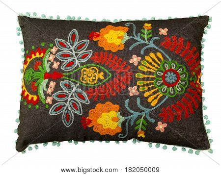 Colorful decorative pillow with a pattern of embroidered flowers isolated on white background.
