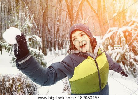 teen boy throwing snow ball outdoor on winter park snowy background
