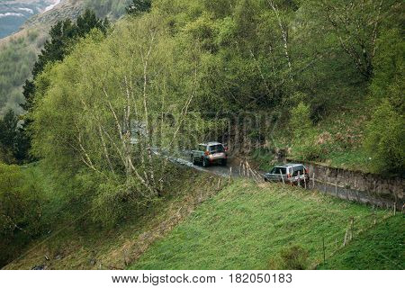 Kazbegi, Gergia - May 23, 2016: Mitsubishi Montero Sport SUV cars driving on country road in summer meadow. Mitsubishi Pajero Sport is a mid-size SUV produced by the Japanese manufacturer Mitsubishi Motors