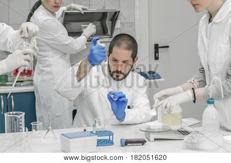 Group of scientists working with liquid test tube samples in laboratory
