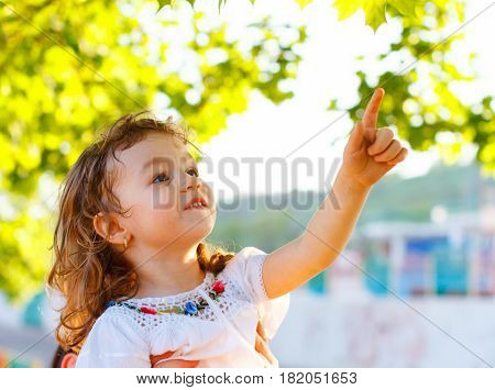 Little girl touching leaves in a spring day