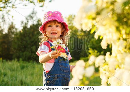 Cute little girl playing with flowers in park