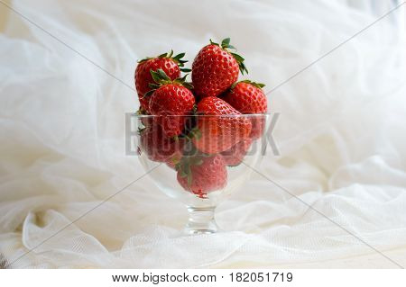 Ripe strawberries in a glass vase. Large strawberries are red and delicious. Berry for diet rich in vitamins.