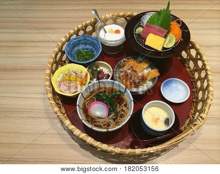 Special Japanese traditional meal on the basket variety of Japanese food Salmon and Tuna sashimi Pork cutlet Tonkatsu rice bowl soba with soup steamed eggs seaweed salad and yogurt top view