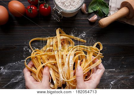 Female Hands Making Fresh Homemade Pasta. Pasta Ingredients On The Dark Wooden Table Top View