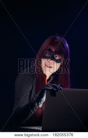 Thief in mask with laptop