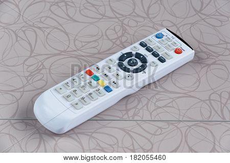 White remote control on white wooden board.