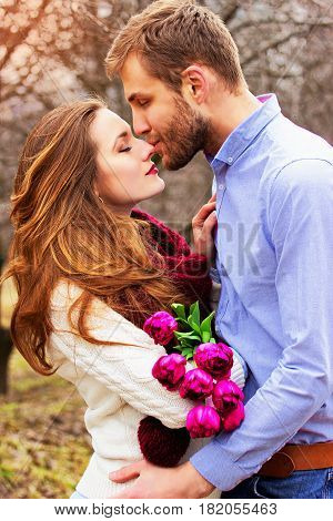 Happy Couple Together. Portrait Of Bearded Man Kissing His Lovely Girlfriend With Flowers On The Gar